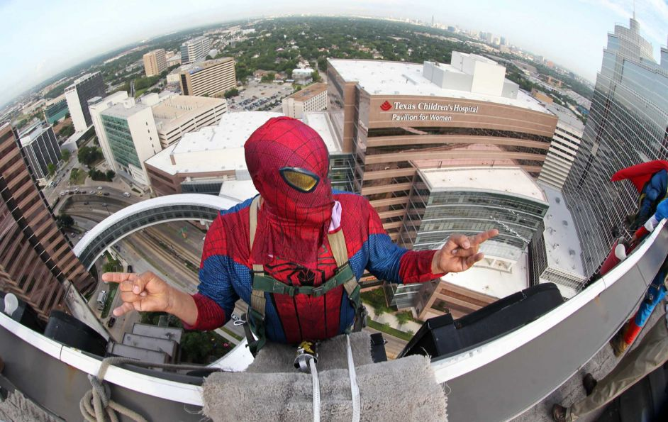 "Gerber Abarca as ""Spiderman"" rehearses his poses while dangling off the building to begin scaling the hospital exteriors to wash windows and surprise patients at Texas Children's Hospital on Friday, July 19, 2013, in Houston.  PHOTO BY MAYRA BELTRAN"